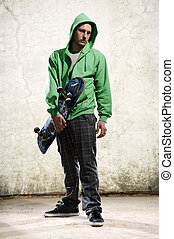 Cool dude skateboarder - Youth stands with skateboard and...