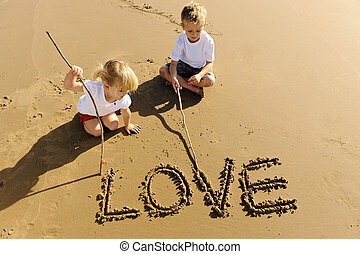 Kids writing in sand - Lovely young brother and sister write...