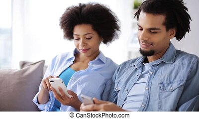 happy couple with smartphones at home - people, technology,...