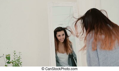 Happy young woman singing in bedroom, looking at mirror. Girl uses hair dryer as microphone. Slow motion.