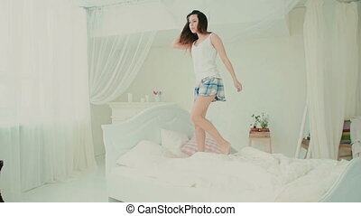 Happy young woman wearing pajamas jumping on her bed. Attractive girl feeling happy, hair rises up. Slow motion.
