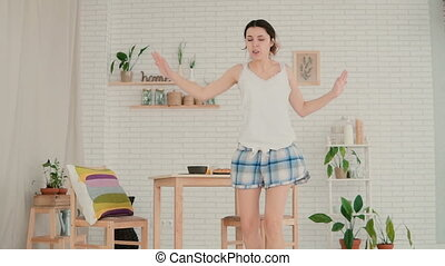 Young happy woman in pajamas dancing at home. Attractive...