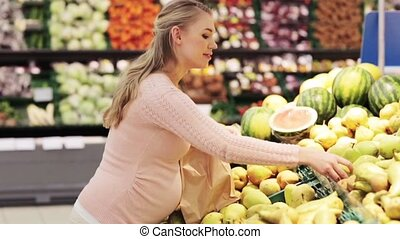 pregnant woman with bag buying pears at grocery - sale,...