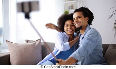 happy couple with smartphone taking selfie at home - family,...