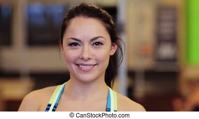 happy smiling young woman at gym - sport, fitness, emotion,...