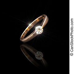 Gold ring with a brilliant on a black background