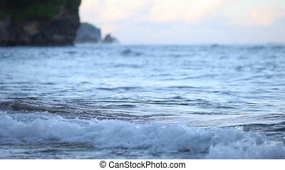 Small ocean waves wash over rocks on the beach at sunset,...