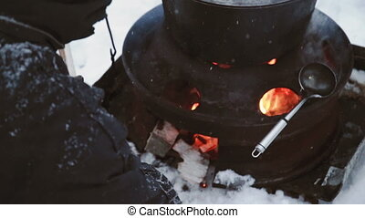 Tourist people cook in pot hanging over campfire fire in winter