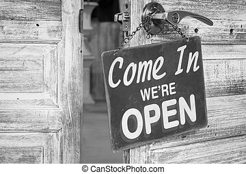 Come In We're Open on the wooden door open, Black and white...
