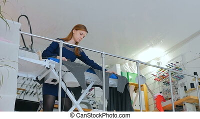 Professional dressmaker, tailor ironing fabric at sewing...
