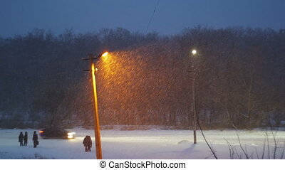 Snow Falls Against the Background of a Lamppost at Night....