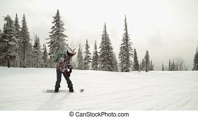 Young female snowboarder riding fresh powder snow in...
