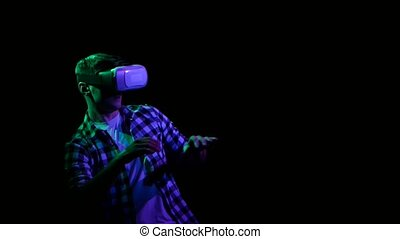 Man playing online games in virtual reality glasses. Black...