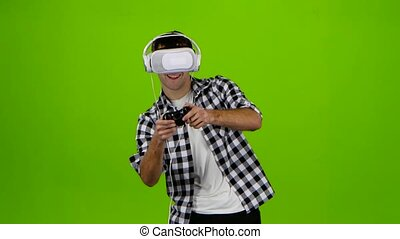 Man plays on gamepad with headphones and vr glasses. Studio...