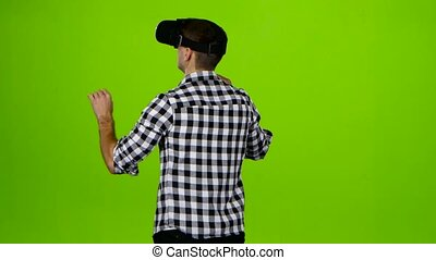 Man in vr glasses on head. Back view. Green screen - Man in...