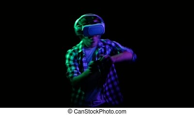 Man plays on gamepad in virtual reality glasses. Green light...