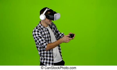 Man plays on gamepad with headphones and in vr glasses - Man...