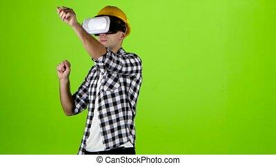 Engineer in yellow helmet works of vr glasses. Green screen...