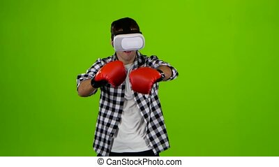 Man plays in a box with vr glasses. Green screen