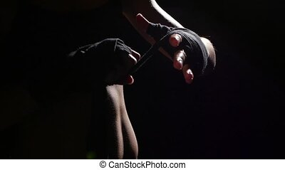 Boxer shakes special bandages on his hands. Silhouette....