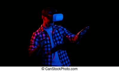 In virtual reality glasses man moves hands. Dark studio -...