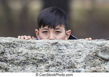 Boy peeks out from behind wall.