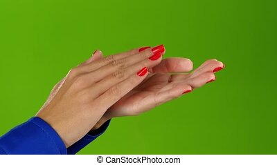 Girl doing applause her hands on a green screen background -...