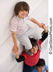 young boys posing line up piggyback top view - happy young...