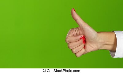 Hand shows thumb up. Green screen background in the studio