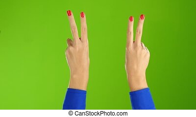 Green screen studio. Two hands show a gesture of peace -...