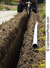 Trencher in action - focus on the pvc conduit