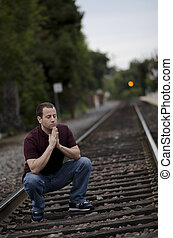 Man stopping to pray train tracks. - Man crouching to pray...