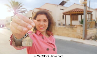 A woman holds the keys to a new home - Happy woman holds the...