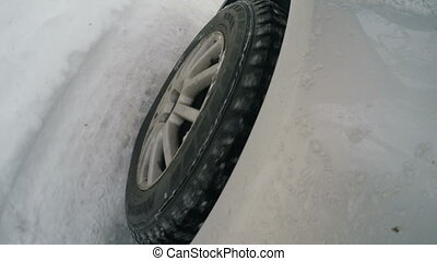 The wheel of the car on the snowy road - View of the wheel...