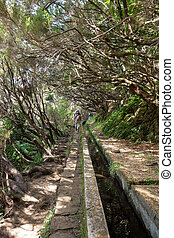 Tourist is walking along irrigation canals. Historic water...