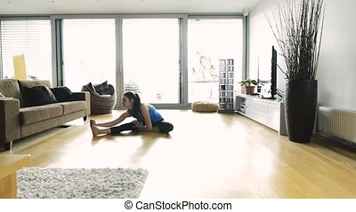 Young woman exercising at home, stretching legs. - Beautiful...