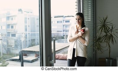 Woman relaxing on balcony holding cup of coffee or tea -...