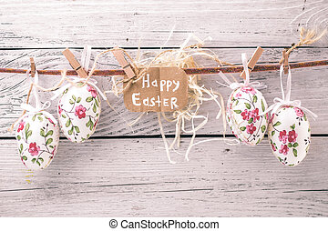 Easter eggs on a string with flowers on a light wooden...