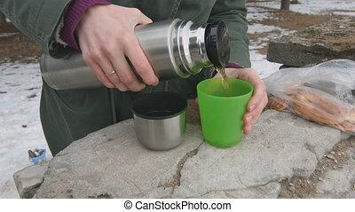 Woman pours hot tea