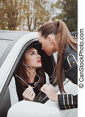 Young beautiful police woman stops car for checking driver...