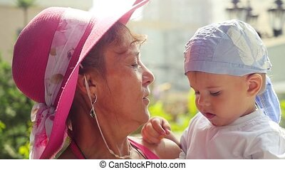 Fashionable happy grandma wearing pink hat holds and tells something grandson in slow motion in sunny summer day.