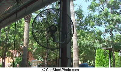 the fan is spinning in the outdoor pavilion