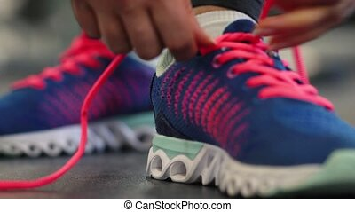 Running shoes - woman tying shoe laces in the gym - Running...