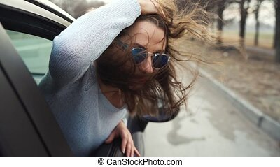 Happy young woman sitting in car passenger seat and looking...