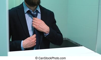 Beared businessman in glasses tying a tie