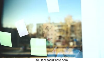 Businesswoman looking at sticky notes on glass board -...