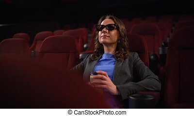 Young woman watches movie 3D at the cinema and drinks...