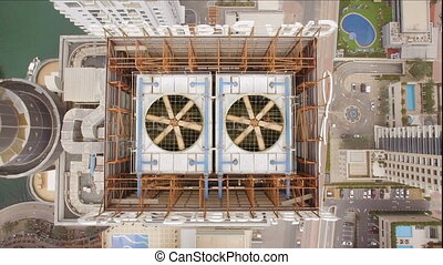 aerial view of two cooling fan spinning on the roof of the skyscraper. To the left of the building you can see the lake and to the right of the pool