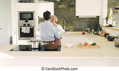 Senior couple in the kitchen cooking and dancing together. -...