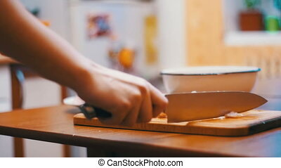 Woman Hands with a Knife Cutting Meat on a Wooden Cutting...